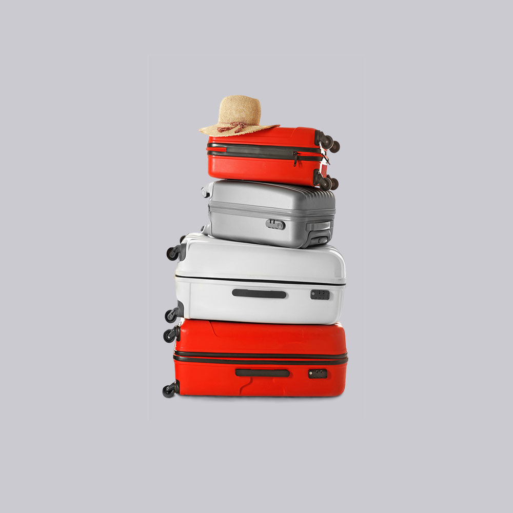 Family suitcases in red, silver and white stacked with a sun hat balanced on top