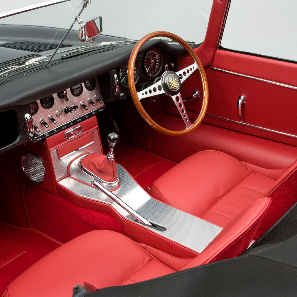 Front seat red leather interior of a classic black sports car funded by specialist car finance